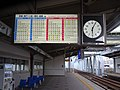 Hanshin Line - Dekijima station - platform (west) with timetable and clock towards the north.jpg