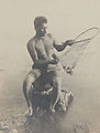 Hawaiian fisherman retrieving fish from small net, 1925.jpg
