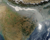 Satellite view of the northern portion of South Asia. The arc of a substantial range of mountains, the Himalayas, dips into the shot, then back up out of view. Immediately beneath, a large region of plains is hidden by a continuous cloud-like opaque mass that has collected along the southern margins of the mountains. It proceeds eastward, staying just south of the Himalayas, then bends due south to reach the Bay of Bengal. Two parts of the mass appear particularly dense, showing up as bright white blobs in the shot.