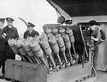 "Hedgehog, a 24-""barreled"" anti-submarine mortar, mounted on the forecastle of the destroyer HMS Westcott, 28 November 1945. The 27-year veteran Westcott claimed the first-ever kill by Hedgehog February 2, 1942, when she sank U-581. Hedgehog anti-submarine mortar.jpg"