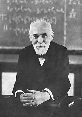 Hendrik Antoon Lorentz voor een collegebord met formules met tensoren uit de algemene relativiteitstheorie. Het boek is mogelijk een deel van zijn leerboek Beginselen der natuurkunde.