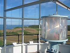 Photograph taken from the lantern room of the lighthouse.  In the foreground on the right is the circular lens surrounding the lamp. The background is the view looking out over the lighthouse grounds and the cliff out to the ocean.