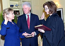 Hillary Clinton taking oath as Secretary of State on January 21, 2009. She is on the left side of the image, facing toward the right. The oath is being administered by Associate Judge Kathryn Oberly, who is standing directly in front of Hillary (on the right side of the photo) and facing toward the left. Bill Clinton, who is standing on both women's side in the background of the image, is holding a Bible.
