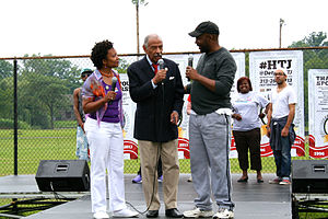History of African Americans in Detroit - Congressman John Conyers speaking on stage alongside Alicia Skillman (l) and Curtis Lipscomb (r) during Hotter Than July 2013 in Detroit, Michigan's Palmer Park