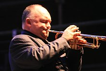 A 45-year-old man is shown in right profile, he is playing a trumpet with his right hand manipulating the valves and his left holding the instrument to his pursed lips. He has sparse thin head hair, his eyes are closed and he wears a brown pin-strip suit jacket. The front of the trumpet is out of shot.