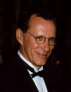 A headshot of a man with brown hair and glasses, wearing a suit and tie, and looking down slightly, while looking at the camera.