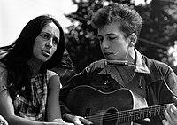 All'aperto, Joan Baez è seduta accanto a Bob Dylan che suona una chitarra acustica, circa anni '60.