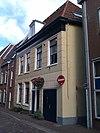 foto van Middeleeuws hoekpand van twee bouwlagen met zadeldak evenwijdig aan de straat