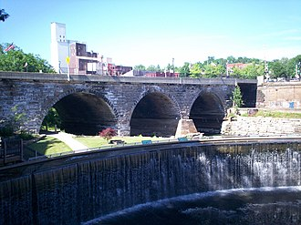 Kent Industrial District - The 1836 dam with the 1877 Main Street Bridge behind. Heritage Park, dedicated in 2005, is located between the dam and bridge.  Water is artificially pumped over the dam.