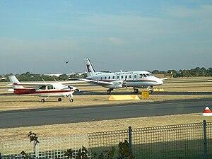 Moorabbin Airport - A King Island Airlines Embraer EMB 110 Bandeirante taxies past a parked Cessna 177RG Cardinal at Moorabbin