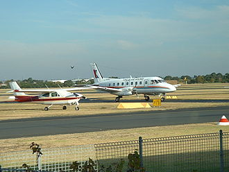 Moorabbin Airport - A King Island Airlines Embraer EMB 110 Bandeirante taxies past a parked Cessna 177RG Cardinal at Moorabbin