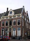 foto van Statig herenhuis met rechte kroonlijst met consoles middenpartij geornamenteerd. Smeedijzeren hekken