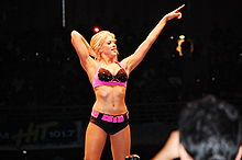 A blonde woman poses on the turnbuckles, while pointing forwards with one hand. She is wearing a black and pink crop top, and black shorts with a pink belt.