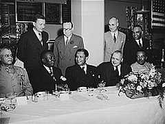 A number of business-suited and uniformed men sit facing the camera along a table
