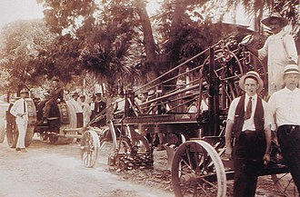 Maxey Dell Moody - Maxey, right in black vest, delivering an Adams road grader from M. D. Moody in St. Augustine, Florida around 1923.