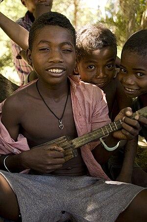 Kabosy - A boy playing a mandoliny or kabosy with full fretting.