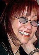 Foto do perfil de uma mulher asiática com óculos de cinquenta e poucos anos.  Ela tem longos cabelos ruivos e mostra um sorriso cheio de dentes.