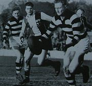 Miller, in the vertically-striped jumper, playing for St Kilda