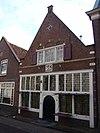 foto van Huis met eenvoudige puntgevel, voorzien van een grotendeels houten pui