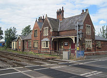 View across the tracks and level crossing of a fine 19th century station building in red brick and with stone mullioned windows, under a roof of Welsh slate.  The platform has gone.