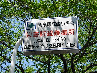 Sign in Japanese, Portuguese, and English in Oizumi, Japan, which has a large lusophone community due to return immigration of Japanese Brazilians. Multilingual Emergency Assembly Area Sign in Oizumi.JPG