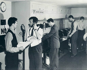 Robert St. John - In the NBC radio newsroom in New York, Robert St. John (at microphone) watches the clock as he prepares to interrupt regular programming with a news bulletin (December 1941).