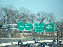 A multilane freeway with a display of three green signs over the road. The left one reads exit 8 east Interstate 287 White Plains Rye three downward arrows, the middle one reads Interstate 87 south Saw Mill Parkway south New York City two downward arrows, and the right one reads exit 8A New York State Route 119 Saw Mill Parkway north Elmsford right lane.