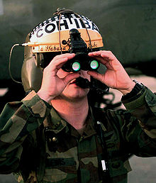 binocular night vision goggles on a flight helmet note the green color of the objective lenses is the reflection of the light interference filters