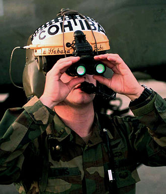 Night vision - Binocular night vision goggles on a flight helmet Note: the green color of the objective lenses is the reflection of the light interference filters, not a glow.