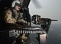 Naval Air Crewman Erik Potter mans a .50-caliber machine gun aboard an MH-60S Sea Hawk helicopter (36716942905).jpg