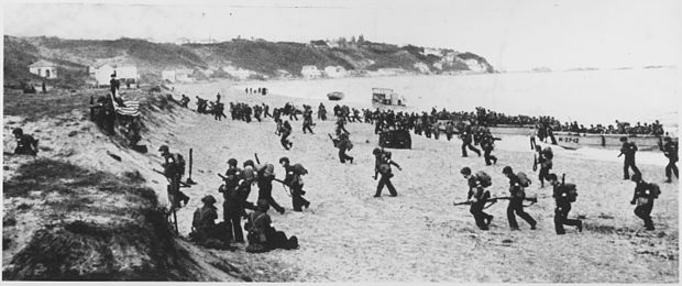 "American troops land on an Algerian beach during Operation Torch. Near Algiers, ""Torch"" troops hit the beaches behind a large American flag ""Left"" hoping for the French Army not fire... - NARA - 195516.jpg"