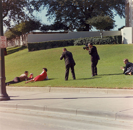 Bill and Gayle Newman drop to the grass and cover their children. - Assassination of John F. Kennedy