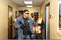 Noe Cordero, foreground, a member of the San Diego Police Department (SDPD) Special Weapons and Tactics team, acts as an assailant while U.S. Navy Master-at-Arms 2nd Class David Scott and other observers follow 130823-N-AA484-011.jpg