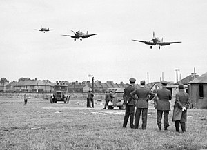 Eagle Squadrons - Personnel of No.121 (Eagle) Squadron look on as three Spitfire Vbs come in to land at RAF Rochford in Essex, after a fighter sweep over northern France during August 1942.