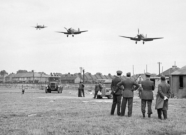 https://upload.wikimedia.org/wikipedia/commons/thumb/3/33/Personnel_of_No.121_%28Eagle%29_Squadron_look_on_as_three_Spitfire_Vbs_come_in_to_land_at_RAF_Rochford_in_Essex%2C_after_a_fighter_sweep_over_northern_France_during_August_1942._D9509.jpg/640px-thumbnail.jpg