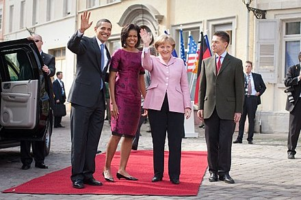 Rathaus in Baden-Baden, Germany, 2009: Barack Obama (the first African American president of the United States), and his wife are welcomed by Angela Merkel (the first woman Chancellor of Germany) and her husband. President and First Lady Obama with Chancellor Merkel.jpg