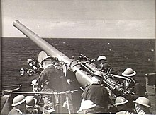 A small naval gun, raised to fire. Nine sailors in helmets are working to prepare the gun for firing.
