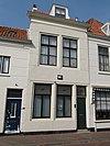 foto van Gepleisterde lijstgevel voor huis van parterre en verdieping met zadeldak