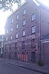 foto van Pakhuis, later gebruikt als fabriek, opgetrokken in baksteen vanaf een gerende, bijna driehoekige plattegrond over vier bouwlagen onder een afgeknot zadeldak