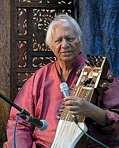 Narayan sits in front of an ornamented partition and speaks into a microphone.