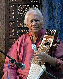 An old man sitting in front of an ornamented partition wall speaks into a microphone and holds a bowed instrument.