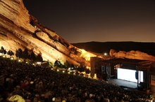 A shot of an outdoor amphitheater taken at dusk, looking down towards a brightly-lit stage. Large red cliffs are visible in the background, sloping down to the right. A large audience is present.