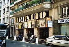 Vue de jour d'un petit cinéma avec son enseigne de lettres majuscules géantes «RIALTO» éteinte.