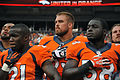 Ronnie Hillman, Ben Garland and Montee Ball listen to national anthem Denver Broncos 2013-08-24.JPG