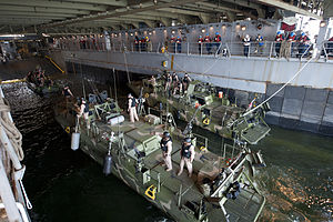 Sailors moor a Riverine patrol boat and Riverine command boats in the well deck of USS Oak Hill.jpg