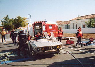 Vehicle extrication - Public demonstration; the roof is removed, a member of the ambulance team holds the oxygen mask and the head of the casualty — Sainte-Soulle, France, September 2001