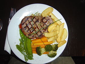 Cuisine of the United States - A sirloin steak dinner, served with sauteed onion, fries, broccoli, carrots, and snow peas, garnished with chives