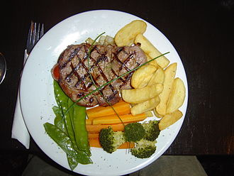 American cuisine - A sirloin steak dinner, served with sauteed onion, fries, broccoli, carrots, and snow peas, garnished with chives