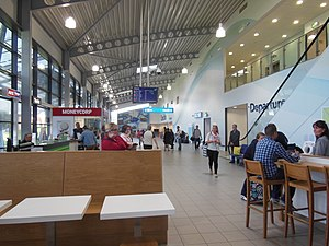 London Southend Airport - Interior of terminal building, seen from café by arrivals, and showing check-in area and escalator to departures.
