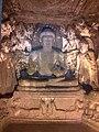 Stone Buddha in padmasana with other deities around at Ajanta Caves.jpg